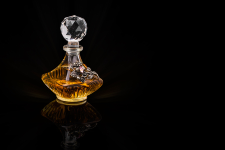 Close Up Shot Of Traditional Luxury Arabic Oud Oil Perfume In A Beautiful Handmade Clear Crystal Glass Jar Bottle and Glass Dropper Isolated On Black Background Antique Style, Text Space 免版税图像