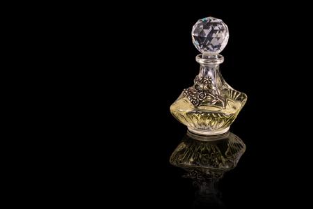Close Up Shot Of Traditional Luxury Arabic Oud Oil Perfume In A Beautiful Handmade Clear Crystal Glass Jar Bottle and Glass Dropper Isolated On Black Background Antique Style, Text Space 스톡 콘텐츠