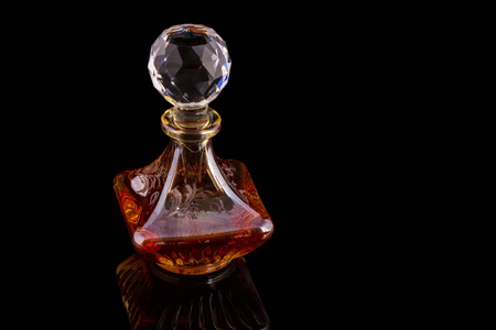 Close Up Shot Of Traditional Luxury Arabic Oud Red Oil Perfume In A Beautiful Handmade Clear Crystal Glass Jar Bottle and Glass Dropper Isolated On Black Background Antique Style, Text Space