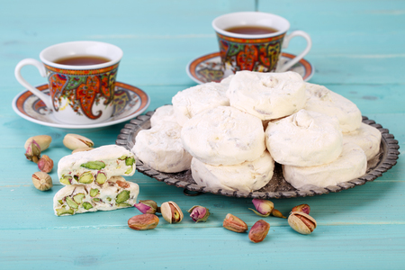 Traditional Iranian and Persian pieces of white nougat dessert sweet candies (Gaz) with Pistachio nuts from Isfahan City and two cups of tea on blue turquoise wood background