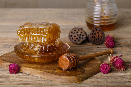 Shot of Honeycombs and honey spoon on a wooden board and table