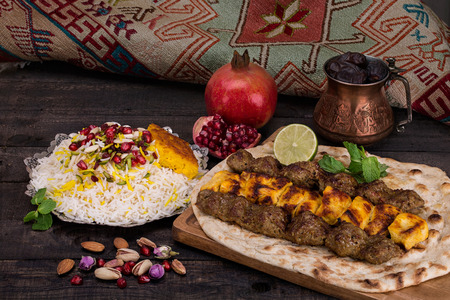 Traditional Middle eastern Persian chicken and lamb meat Shashlik Kebab (skewered meat) BBQ Grill on flat pita bread and saffron rice and tahchin and pomegranate on a dark background. Iranian cuisine Imagens