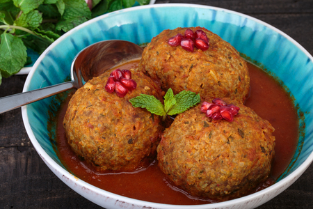Koofteh Tabrizi Large Meatballs Stuffed With Dried Fruits, Berries And Nuts In Tomato Turmeric Broth A Traditional Azeri And Iranian Dish Served In Turquoise Bowl Garnished With Pomegranate