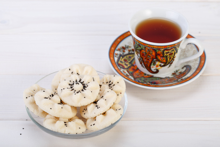 Flower Shaped Persian Sweet Rice Cookies (Naan Berenji) with Poppy Seeds and a paisley design cup and saucer tea on white wooden background Stock Photo