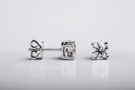 Pair of Diamond and white gold stud earrings on white background 免版税图像
