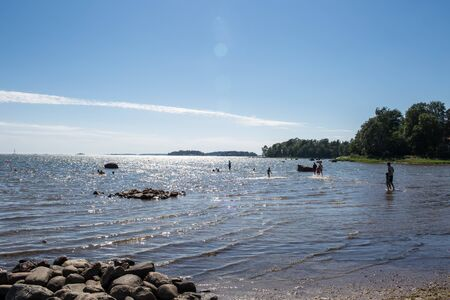 A beautiful beach and clear blue sky with people having fun and activities in  Helsinki Finland during long days summer