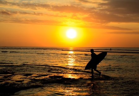 A surfer walking on the beach at sunset photo