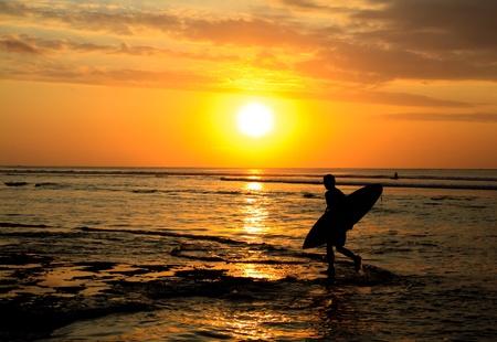 Un surfeur marcher sur la plage au coucher du soleil