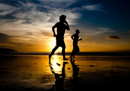 Two men running on Jimbaran beach at sunset with phone photo