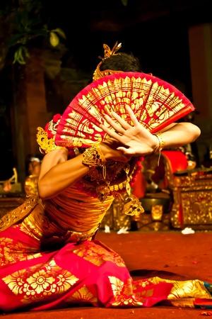 Une danseuse legong assis derrière son ventilateur