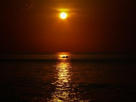 Petit bateau traversant le soleil au coucher du soleil à Bali de Jimbaran