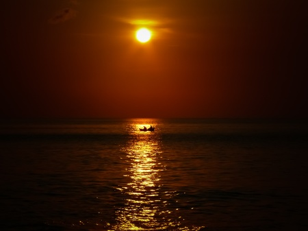 Small boat crossing the sun at sunset in Jimbaran Bali