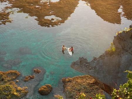 Two surfers talking in Uluwatu beach pools