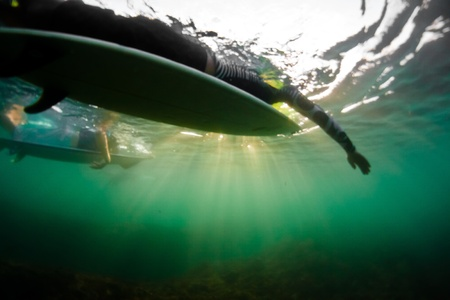 View of two surfers paddling from underwater shot