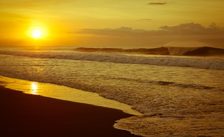 Wave breaking as the sunrise on a paradisiac beach