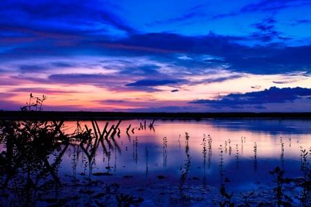Un coucher de soleil pourpre d'une rive du lac à Bali Banque d'images