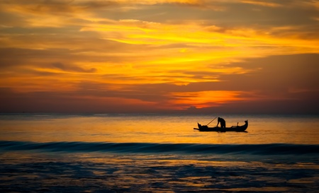 Ombre de bateau du pêcheur un petit sur la mer avec une étonnante ciel du coucher du soleil derrière