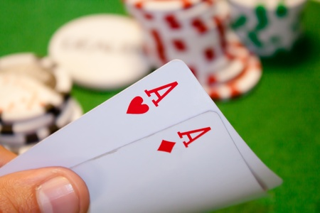 Pocket aces pair with stack money in the background photo