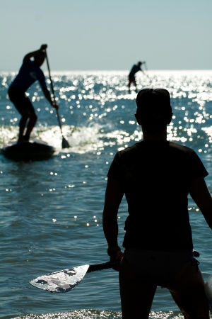 sup: Three stand up paddlers shadows on the water