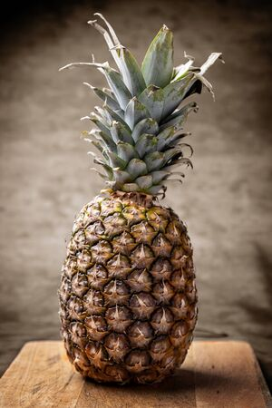 Pineapple presented on a wooden board over brown background