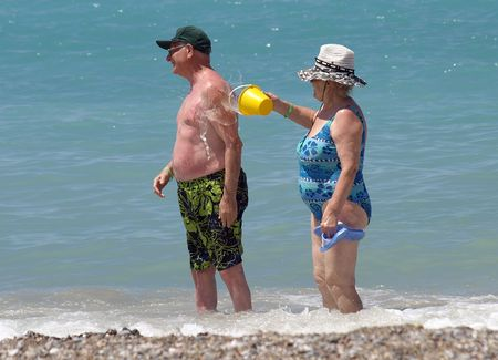 Happy retired couple enjoyed by water on a coast of ocean