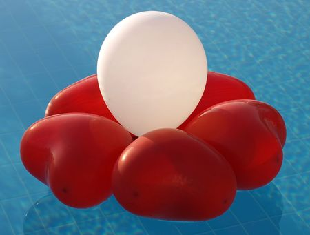 inflated: Abstract decoration of inflated heart-shaped balloons on a water.