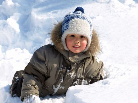 Funny little boy playing in snow, outdoors in winter. Stock Photo