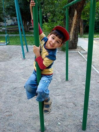 children playground: Little boy playing on the vertical bar at the playground. Stock Photo