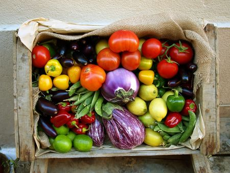 Just harvested fresh and ripe biological vegetables and fruits in a wooden box.