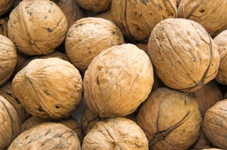 Closeup of brown raw walnuts background photo