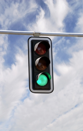 Green traffic lights against blue sky backgrounds with clipping path photo