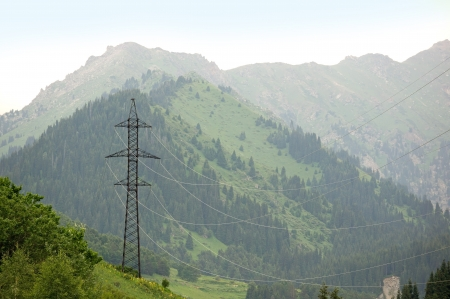 High-voltage power line through Alps mountains photo