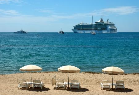 Mediterranean beach with three umbrellas in Cannes, France