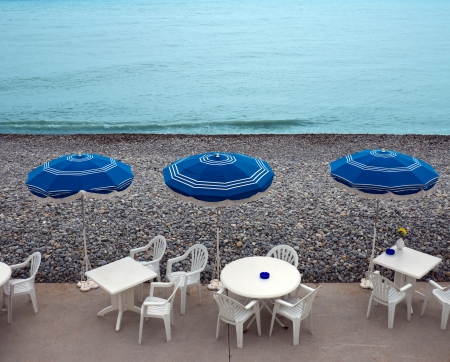 Lounge chairs, tables and parasol on the beach, southern France photo