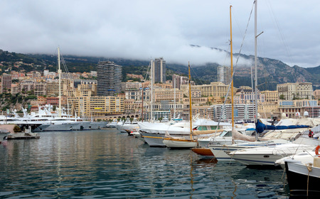 Monte Carlo, Monaco - Fashionable yachts in the port Hercules and view on the city. photo