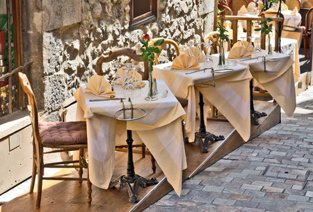 Restaurant on the street in Cannes with tables and chairs photo