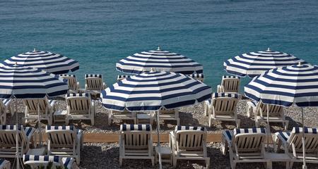 Beach with blue umbrellas near Promenade des Anglais in city of Nice, France.