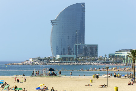 bathers: BARCELONA, SPAIN - JULY 12, 2015: Barceloneta Beach and Hotel Vela, designed by Architect Ricardo Bofill. Located on the new entrance of Barcelonas Port. Editorial