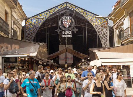 market vendor: BARCELONA, SPAIN - JULY 6, 2015: Main gate at La Boqueria market. Market has been known since 1217. Now - one of the citys foremost tourist landmarks. Editorial