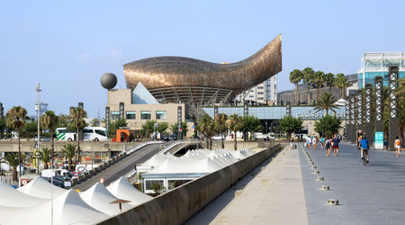 BARCELONA, SPAIN - JULY 12, 2015: Promenade and Frank Gehrys modern El Peix dOr sculpture is located in Barcelonas Vila Olimpica, Olympic Village for the 1992 Olympic games. Editorial
