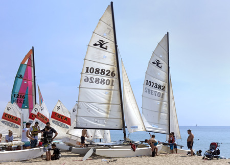 fun activity: BARCELONA, SPAIN - JULY 13, 2015: People prepare yachts for surfing. Municipal Nautical Barcelona - surfing club for children and adult. Located in Park Poblenou, Barcelona, Spain.