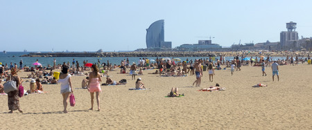 bathers: BARCELONA, SPAIN - JULY 4, 2015: A crowd of bathers in La Barceloneta Beach in Barcelona, Spain. This popular beach hosts about 500,000 visitors from everywhere during the summer season.