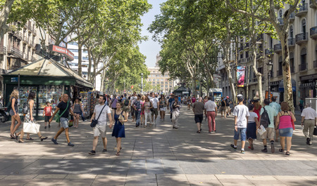 BARCELONA, SPAIN - JULY 6, 2015: Hundreds of people promenading in the busiest street of Barcelona, the Ramblas. The street extends 1.2 kilometers connects the Placa de Catalunya in the centre with the Christopher Columbus Monument at Port Vell. Editorial