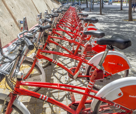 public service: BARCELONA, SPAIN - JULY 4, 2015: Public Service Vehicles bicycles Vodafone Bicing. Bicing is the name of a bicycle sharing system in Barcelona inaugurated on March 22, 2007.
