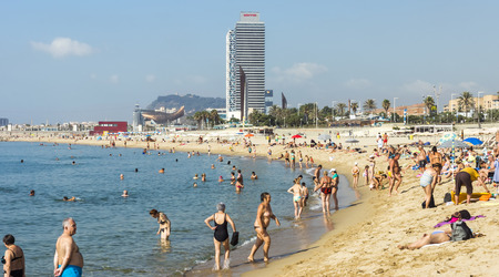 bathers: BARCELONA, SPAIN - JULY 13, 2015: Barceloneta Beach and skyscraper Torre Mapfre in the Olympic Port. It is named after its owner, Mapfre, an insurance company.