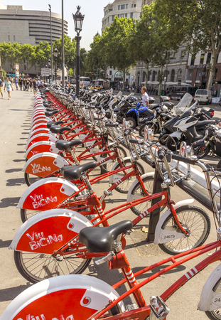 public service: BARCELONA, SPAIN - JULY 6, 2015: Public Service Vehicles bicycles Vodafone Bicing. Bicing is the name of a bicycle sharing system in Barcelona inaugurated on March 22, 2007.