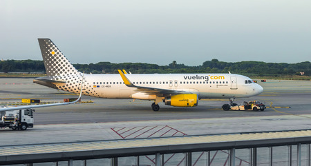 center position: BARCELONA, SPAIN - JULY 16, 2015: Aircraft of Vueling Airlines at the gate in Terminal T1 of El Prat-Barcelona airport.