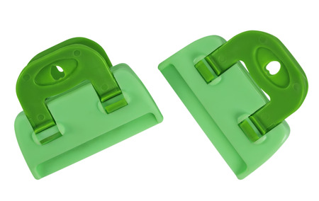 clench: Green plastic clamps isolated on white background. Clipping path included for your design. Stock Photo