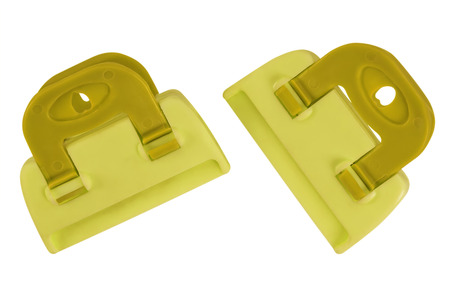 gripe: Yellow plastic clamps isolated on white background.