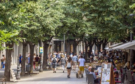 GIRONA, SPAIN - JULY 6, 2016: Hundreds of people promenading in the busiest street of Girona, the Ramblas.